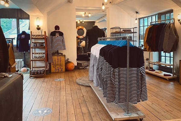 Inside of Berties' shop, light-wooden floors and wool jumpers and other products