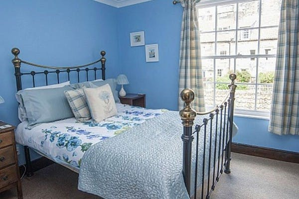 Light blue walled room with window and bed